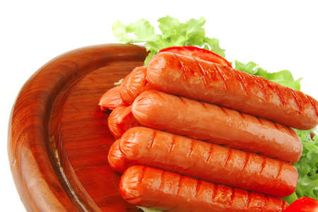 grilled sausages served on wooden plate with vegetables photo