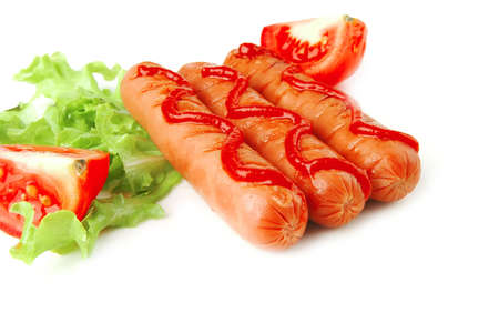 row of three sausages served with tomato and salad