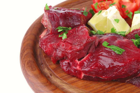 uncooked small beef chunks on wooden plate photo