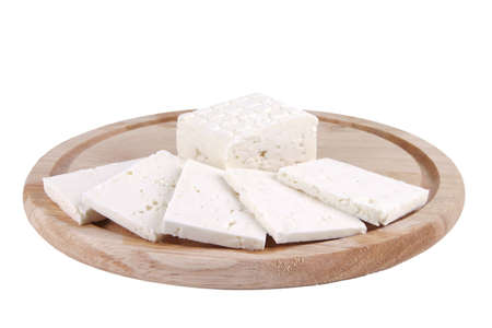 sliced white goat cheese on wooden plate Stock Photo