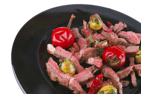 roast meat on black dish wuth red hot pepper and olives photo