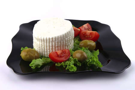 soft feta cheese on black dish with tomatoes photo
