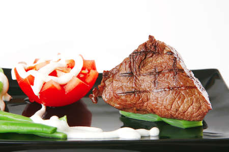 charbroiled: fillet mignon served on a white plate with tomato Stock Photo