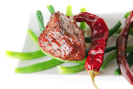 served roast veal fillet on a white plate with peppers photo