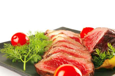finocchio: a fette di carne fresca sulla piastra scuro con pomodoro e finocchio