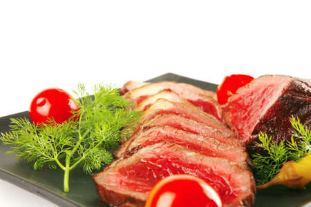 sliced fresh meat on dark plate with tomato and fennel