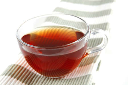 hot black tea inside transparent cup served on tissue photo