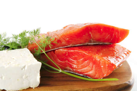 sinlge pink salmon bit on a big wooden dish with white cheese photo