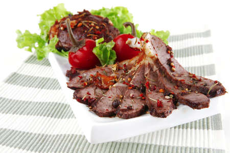 steak slices served on plate over textile  photo
