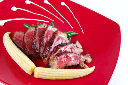 meat served with beans and corns on red ceramic plate photo