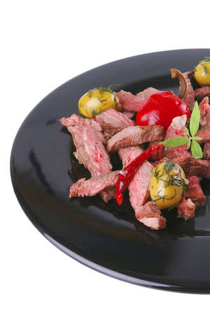 beef meat served on black plate over white photo