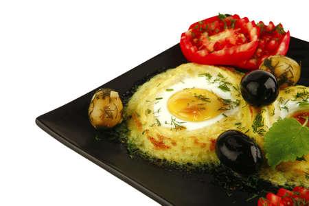 mashed potatos with fried eggs on black photo