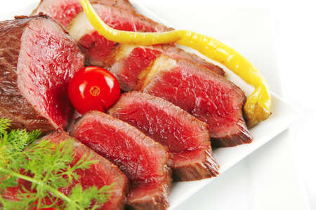 grilled meat on white plates with peppers and tomato photo
