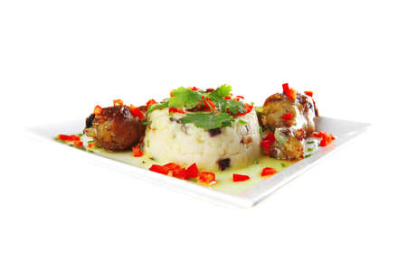 chicken drumsticks served on white plate with mash photo