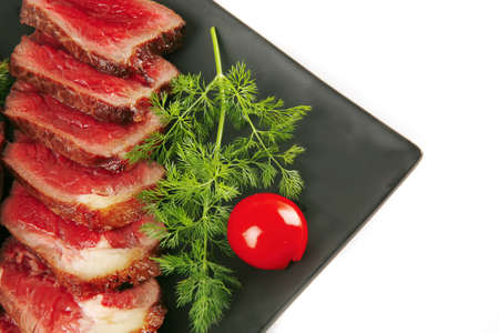sliced fresh meat on dark plate with tomato and fennel photo