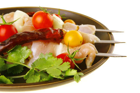 raw chicken kebabs served on dark plate with vegetables photo