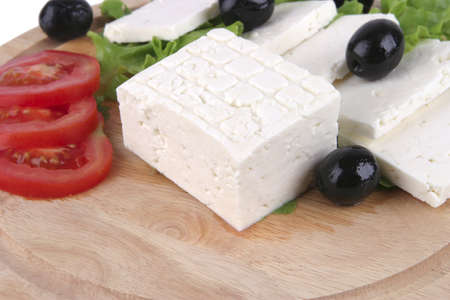 white cheese with olives and tomato on wood photo
