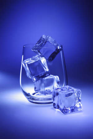 ices: crystal glass and ices on blue background Stock Photo