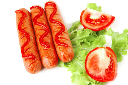 sausages served with ketchup salad and tomato  photo