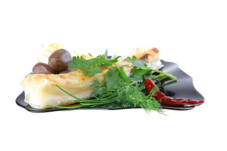 cannelloni in yellow cheese served with pepper and olives photo
