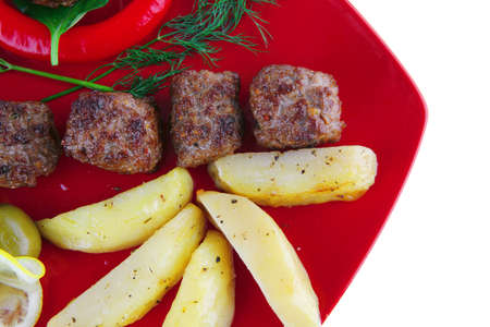 roast cutlets on red dish with peppers and potatoes photo