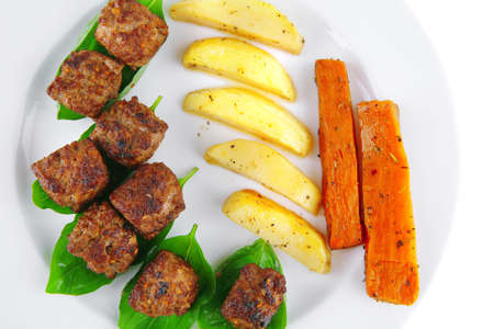 grilled meatballs on white plate with basil and potatoes photo