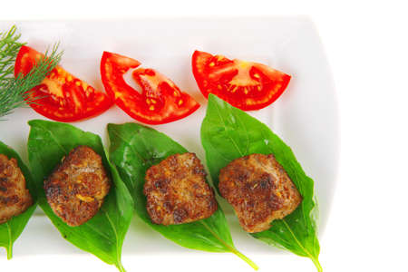 roasted beef cutlets on white with tomatoes and lemon photo