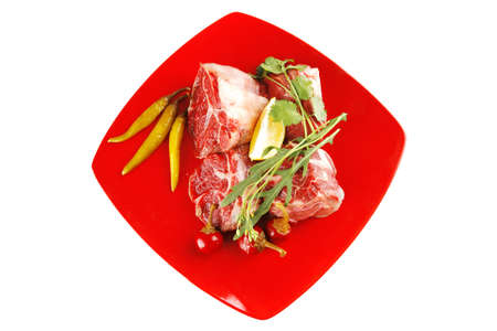 raw beef meat medallion on red plate photo