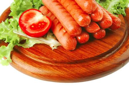 saucisses grillés servi sur une plaque en bois sur blanc