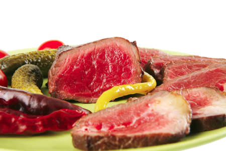red beef slices on green dish with peppers photo