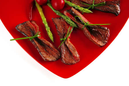 meat slices and asparagus on red over white photo