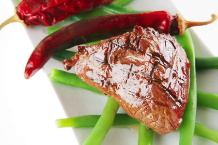 fillet mignon served on a white plate with peppers photo
