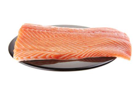 big salmon chunk on black plate over white