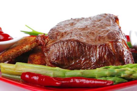 carne asada: barbacoa de carne de vacuno en rojo con espárragos sobre blanco