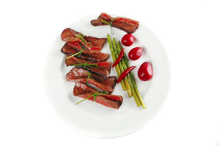 curved meat slices on white dish with vegetables photo