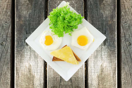 fried eggs and gold cheese on white plate photo