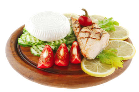 grilled salmon and greek cheese on wooden plate photo