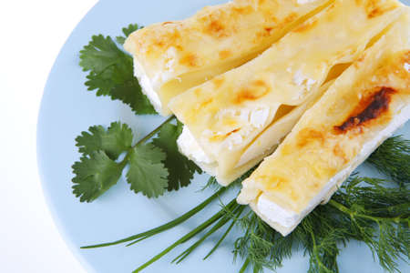 cannelloni in yellow cheese served with greenery photo