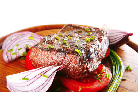 meat dish: beef fillet served on white plate wooden tomato