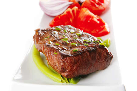 steak plate: roast beef meat served with tomato on ceramic