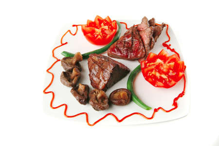 fillet mignon served on a white plate with tomatoes photo
