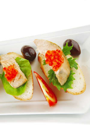 salmon chunks and caviar on baguette with olives photo