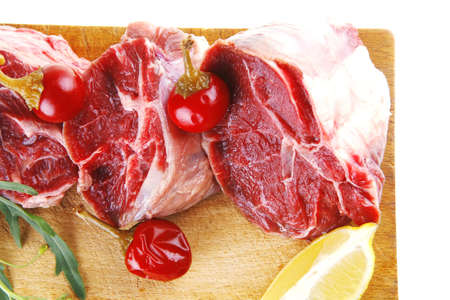 fresh raw beef meat chunks on wood plate photo
