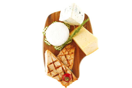 grilled salmon and french cheeses on wooden plate photo