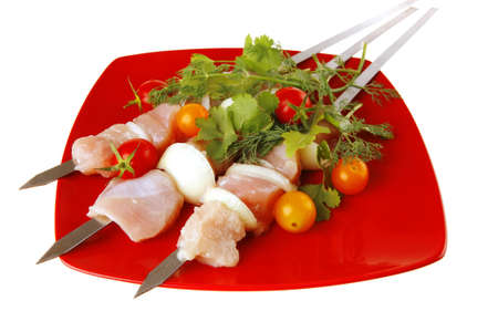 raw  chicken kebabs served with cherry and greenery photo