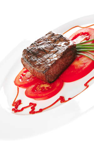 beef meat served on white plate with tomato   photo