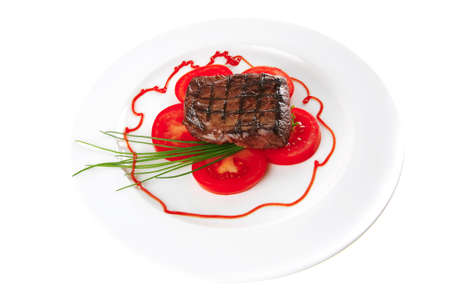 roasted meat served with tomato on ceramic plate photo