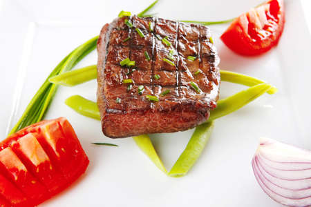 roast beef fillet served with tomato on white photo