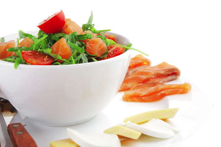green salad with smoked salmon and bread in white bowl photo
