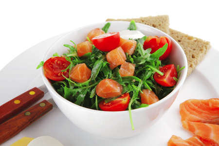 green salad with salmon and tomatoes in white bowl photo
